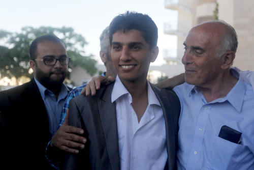 Arab Idol winner Palestinian Mohammed Assaf, center, is welcomed by Muneb Al-Masri, a Palestinain businessman, right, upon his arrival to Rafah crossing point on the border between Egypt and the southern Gaza Strip, Tuesday, June 25, 2013. Huge crowds of Gazans gave a gleeful welcome Tuesday to the first Palestinian winner of the Arab Idol talent contest, thronging the territory's border crossing with Egypt and the singer's home in hopes of embracing him, but internal politics surfaced quickly. Assaf's victory in the popular contest Saturday sparked huge celebrations in the West Bank and Gaza, giving Palestinians a sense of pride. (AP Photo/ Hatem Moussa)