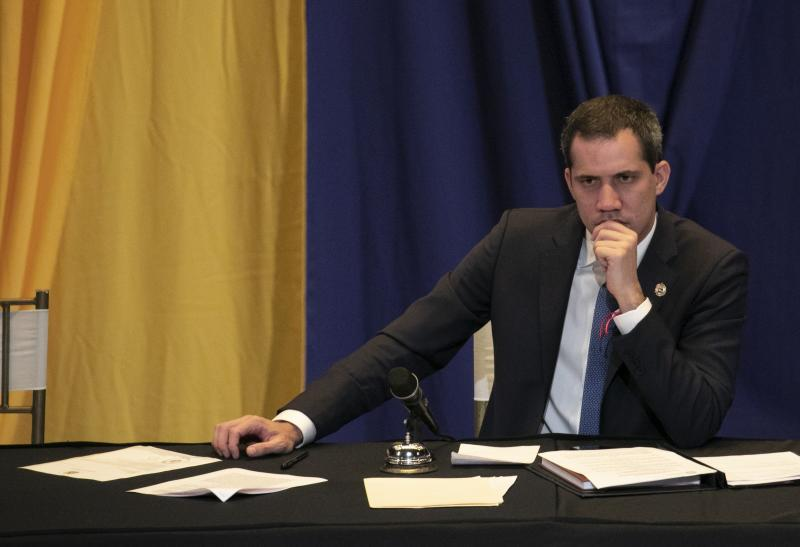 FILE - In this March 4, 2020 file  photo, opposition leader Juan Guaido listens during a legislative session being held at a religious, private school in Caracas, Venezuela, an alternative location due to the government continuously blocking their access to National Assembly chambers. Guaidó said Monday, May 11, 2020 that two U.S.-based political advisers have resigned following a failed incursion into Venezuela aimed at capturing President Nicolás Maduro. (AP Photo/Ariana Cubillos, File)