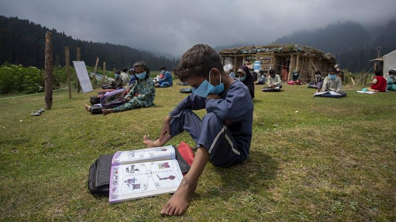 A boy reads a book during a class in the outdoors.