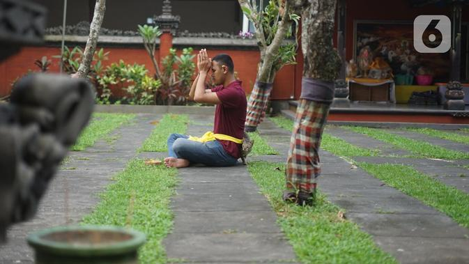 Umat Hindu berdoa di Pura Widya Dharma yang sepi di kawasan Cibubur, Jakarta Timur, Selasa (24/3/2020). Pembatasan aktivitas menjelang Hari Raya Nyepi tahun baru Saka 1942 dilakukan sesuai dengan imbauan pemerintah untuk antisipasi penyebaran virus corona Covid-19. (Liputan6.com/Immanuel Antonius)