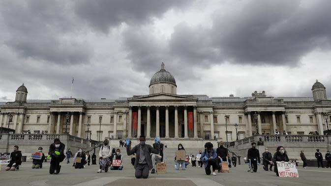 Demonstran berlutut untuk memprotes kematian George Floyd di Trafalgar Square, London, Inggris, Jumat (5/6/2020). Kematian pria kulit hitam George Floyd saat ditangkap oleh polisi Amerika Serikat memicu kemarahan di sejumlah negara. (AP Photo/Kirsty Wigglesworth)