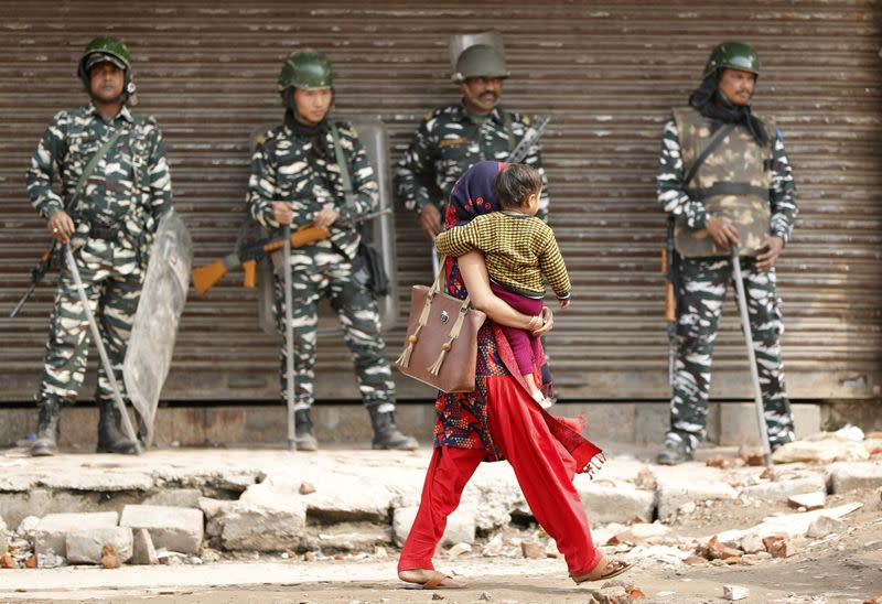 A woman carrying a child walks past security forces in a riot affected area after clashes erupted between people demonstrating for and against a new citizenship law in New Delhi
