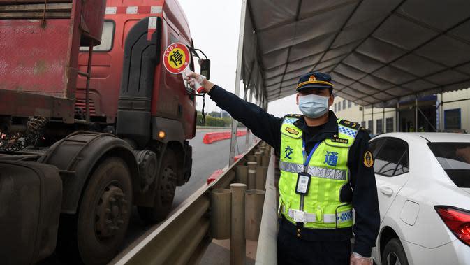 Seorang staf memandu sejumlah kendaraan untuk berhenti di tepi jalan guna mengukur suhu tubuh para pengemudinya di dekat sebuah gerbang tol sebagai upaya memerangi wabah di Nanning, Daerah Otonom Etnis Zhuang Guangxi, China selatan, pada 1 Februari 2020. (Xinhua/Lu Boan)