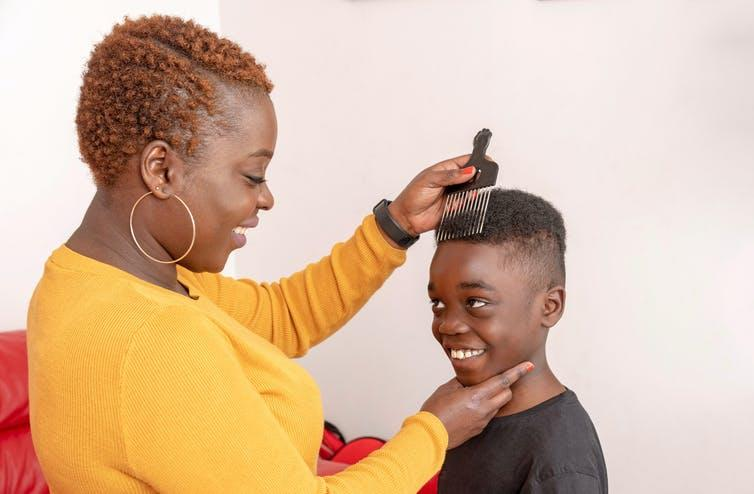 Mother combing child's hair with afro comb