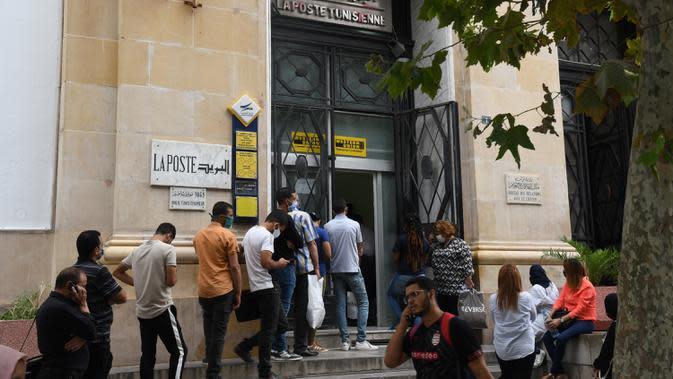 Orang-orang yang mengenakan masker mengantre untuk memasuki kantor pos di Tunis, Tunisia, pada 5 Oktober 2020. Perdana Menteri Tunisia Hichem Mechichi pada 3 Oktober mengumumkan serangkaian langkah untuk membatasi penyebaran cepat COVID-19 di negara tersebut. (Xinhua/Adel Ezzine)