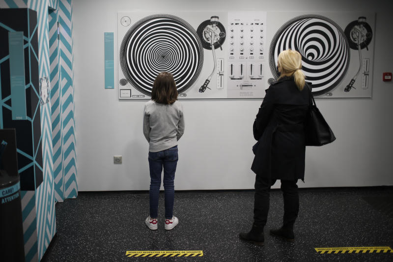 Visitors look at artwork at the Illusion museum Monday, May 11, 2020 in Paris. The French began leaving their homes and apartments Monday for the first time in two months without permission slips as the country began cautiously lifting its virus lockdown. Small museums are allowed to reopen Monday if respecting the protective measures. (AP Photo/Rafael Yaghobzadeh)