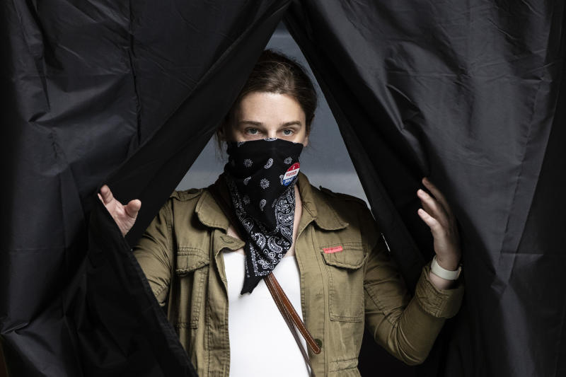 Jenn McCullough, wearing a protective face mask as a precaution against the coronavirus, steps from the voting booth after casting her ballot in the Pennsylvania primary at the Kimmel Center in Philadelphia, Tuesday, June 2, 2020. (AP Photo/Matt Rourke)