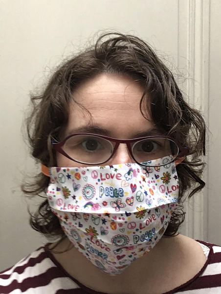 In this photo taken on Thursday, March 19, 2020, Anais Moyson, wears a mouth mask, meant to help protect from the spread of COVID-19, that she produced on her sewing machine at home in Antwerp, Belgium. Moyson is making masks for family and friends and hopes to be able to produce enough to deliver to caregivers and local doctors. Belgium currently has a need for the masks due to a shortage in supply of industrially made masks. For most people, the new coronavirus causes only mild or moderate symptoms, such as fever and cough. For some, especially older adults and people with existing health problems, it can cause more severe illness, including pneumonia. (Anais Moyson via AP)