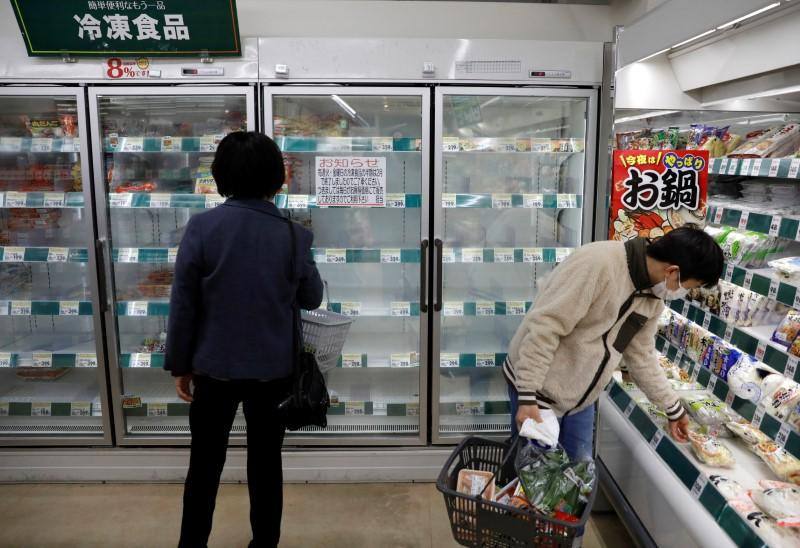 A shopper wearing a protective face mask, following an outbreak of the coronavirus disease, is seen next to an empty shelves of frozen foods at a supermarket in Tokyo, Japan