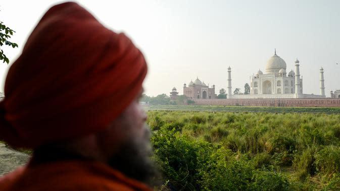 Seorang pria berdiri di seberang Taj Mahal dari tepi sungai Yamuna di Agra, Jumat (4/5). India tengah dirundung kekhawatiran akan perubahan warna pada salah satu situs bersejarah dunia, Taj Mahal karena terpapar polusi. (AFP/CHANDAN KHANNA)