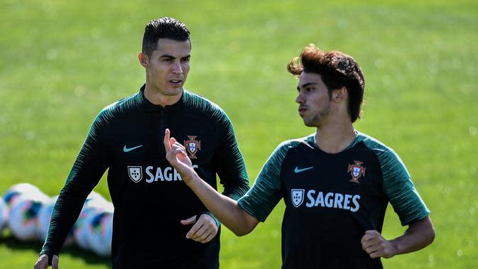 Penyerang Portugal Cristiano Ronaldo (kiri) berbincang dengan Joao Felix saat latihan bersama jelang menghadapi Luksemburg pada laga kualifikasi Euro 2020 di Oeiras, Portugal, Rabu (9/10/2019). Portugal akan menghadapi Luksemburg pada 12 Oktober 2019. (Patricia De Melo Moreira/AFP)