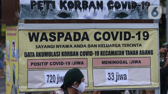 Warga duduk di depan tanda peringatan bahaya COVID-19 di sekitar Pasar Blok A Tanah Abang, Jakarta, Selasa (1/9/2020). Guna meningkatkan kewaspadaan warga, muspida kecamatan Tanah Abang memajang peti mati dilengkapi data jumlah korban COVID-19 di wilayah tersebut. (Liputan6.comHelmi Fithriansyah)