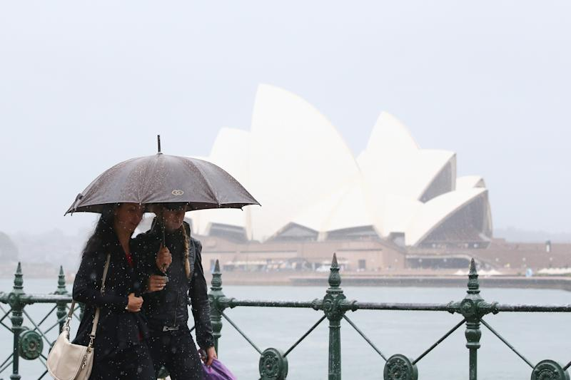 A stock image of people with umbrellas walk past the Sydney Opera House in the rain.