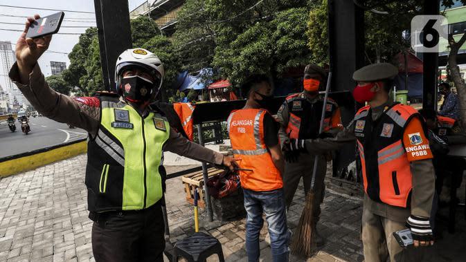 Petugas memotret warga pelanggar Pembatasan Sosial Berskala Besar (PSBB) yang terjaring razia masker di wilayah Tanah Abang, Jakarta, Senin (14/9/2020). Razia tersebut guna menekan kasus penyebaran COVID-19 di Jakarta pada masa PSBB. (Liputan6.com/Johan Tallo)