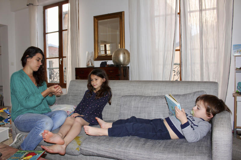 In this photo taken Thursday April 30, 2020 Mathilde Manaud plays on a sofa with her children Mila, 7, and Andre, 3, in Paris. As France prepares to start letting public life resume after eight weeks, many parents are deeply torn over a question without a clear or conclusive answer: Should I send my child back to school?  The French government is easing some of the closure and home-confinement orders it imposed March 17 to curb coronavirus infections, with businesses permitted to reopen, residents cleared to return to workplaces and schools welcoming some students again starting Monday. (AP Photo/Oleg Cetinic)
