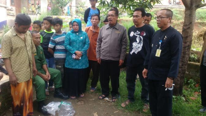 Plt Camat Ujung Berung Didin Dikayuana menyaksikan ular weling yang telah dievakuasi warga dibungkus ke dalam plastik benin. (Istimewa)