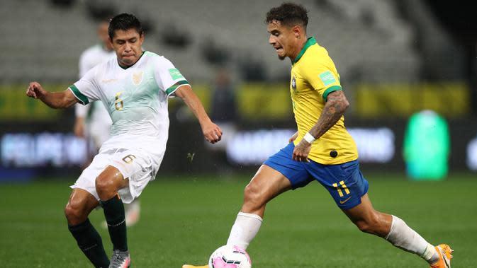 Gelandang Brasil, Philippe Coutinho, berebut bola dengan pemain Bolivia, Diego Wayar, pada laga kualifikasi Piala Dunia 2020 di Corinthians Arena, Sabtu (10/10/2020) pagi WIB. Brasil menang 5-0 atas Bolivia. (AFP/Buda Mendes/pool)