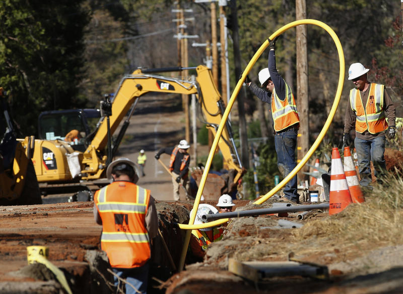 FILE - In this Oct. 18, 2019, file photo, Pacific Gas and Electric Company workers bury utility lines in Paradise, Calif. Pacific Gas and Electric said Tuesday, Feb. 18, 2020, that it expects to become more profitable than ever after it emerges from bankruptcy and pays off more than $25 billion in losses sustained in catastrophic wildfires ignited by its outdated equipment. (AP Photo/Rich Pedroncelli, File)