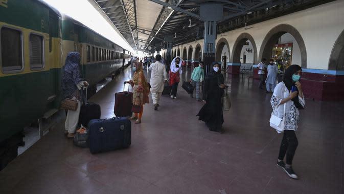 Penumpang mengenakan masker saat menunggu kereta di Stasiun Rawalpindi, Pakistan, Rabu (20/5/2020). Pakistan kembali membuka layanan kereta setelah pemerintah melonggarkan kebijakan lockdown jelang Idul Fitri. (Aamir QURESHI/AFP)