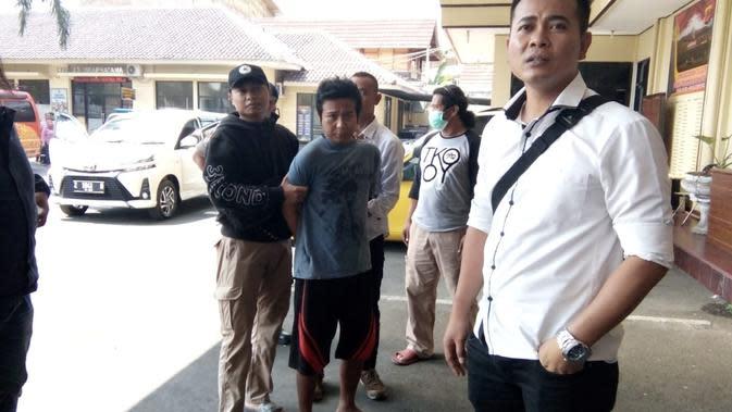 Sidik Nugraha, nampak tertunduk lesu setelah petugas satuan reserse kriminal Kota Tasikmalaya, menangkaonya dalam dugaan kasus pelemparan cairan sperma di Tasikmalaya, Jawa Barat (Liputan6.com/Jayadi Supriadin)