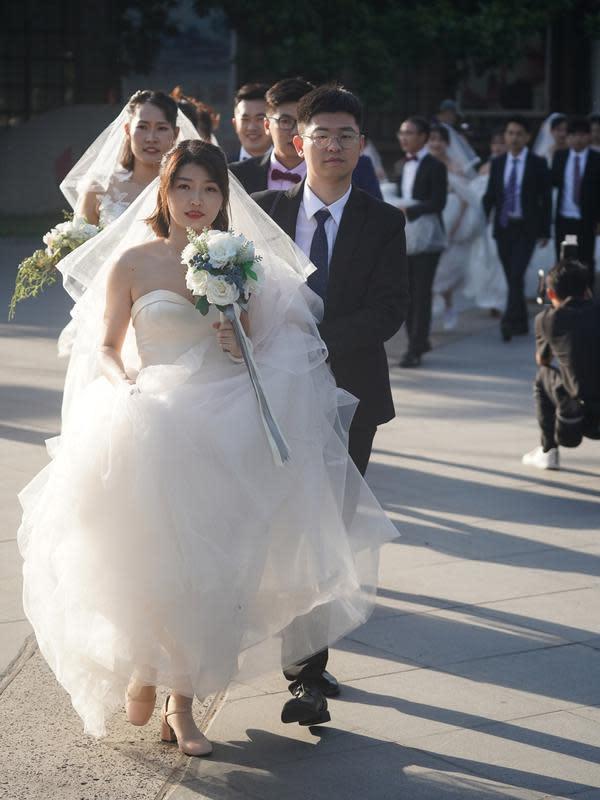 Beberapa pasangan pengantin bersiap untuk berfoto di Nanjing, Provinsi Jiangsu, China timur, (19/5/2020). Sebanyak 15 pasangan pengantin pada Selasa (19/5) berfoto bersama di Nanjing menjelang upacara pernikahan massal mereka yang dihelat pada 20 Mei. (Xinhua/Ji Chunpeng)