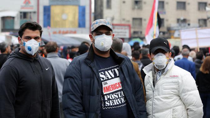 Sejumlah warga Irak mengenakan masker di sebuah jalan di Baghdad, Irak, (25/2/2020). Irak mengumumkan empat kasus baru COVID-19 di Provinsi Kirkuk, wilayah utara, pada Selasa (25/2), sehingga total pasien terinfeksi di negara itu bertambah menjadi lima orang. (Xinhua/Khalil Dawood)