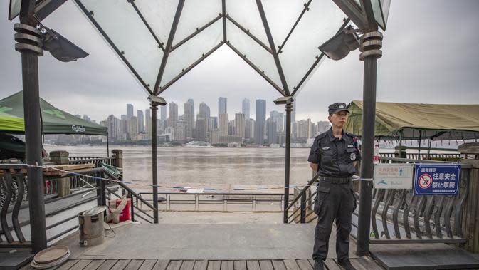 Seorang petugas berjaga di dekat tepi Sungai Yangtze di Kota Chongqing, China barat daya (18/8/2020). Kota Chongqing dilanda banjir parah. Status tanggap darurat Level I dikeluarkan pada Selasa (18/8) untuk pengendalian banjir. (Xinhua/Huang Wei)