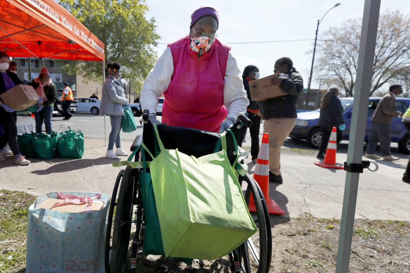 In this Tuesday, May 12, 2020, photo, Linda Shine secures the second bag of food to her wheelchair after visiting a food giveaway sponsored by the Greater Chicago Food Depository in the Auburn Gresham neighborhood of Chicago. Across the country, food insecurity is adding to the anxiety of millions of people, according to a new survey that finds 37 percent of unemployed Americans ran out of food in the past month, while 46 percent worried that they would. The nationwide unemployment rate on Friday was 14.7 percent, the highest since the Great Depression.(AP Photo/Charles Rex Arbogast)