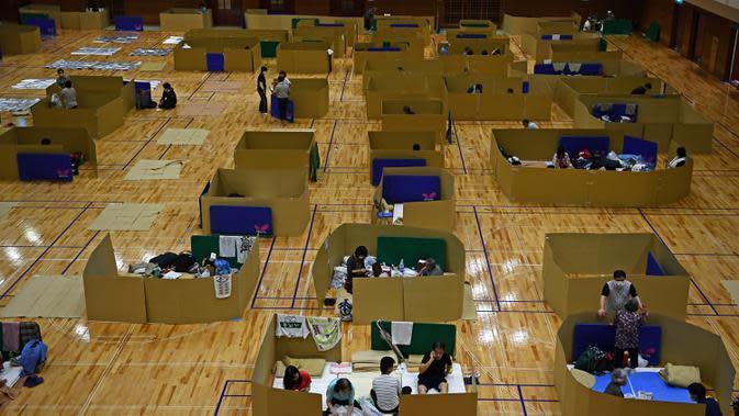 Penduduk setempat berlindung di pusat evakuasi dengan kotak kardus untuk menjaga jarak di sebuah gimnasium kota Yatsushiro di prefektur Kumamoto, Jepang, Senin (6/7/2020). Hujan deras menghambat operasi pencarian dan penyelamatan korban banjir dan tanah longsor di Kumamoto. (Charly TRIBALLEAU/AFP)
