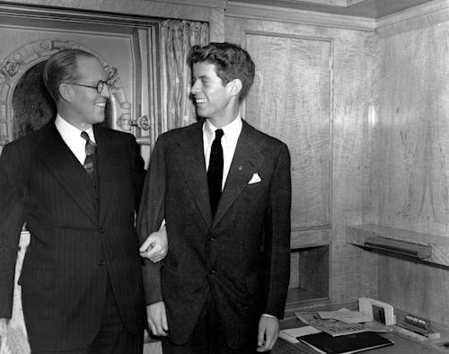 "REMOVES ERRONEOUS REFERENCE TO IMMIGRANT - FILE - In this Jan. 5, 1938 file photo, Joseph P. Kennedy, left, U.S. Ambassador to Great Britain, stands with his son, John F. Kennedy, in New York. Kennedy, born in 1917, was the second son, and one of nine children, of business tycoon Joseph P. Kennedy. When first son Joseph Jr. was killed during World War II, Jack became the designated heir. Himself a Navy veteran and survivor of a collision with a Japanese destroyer, he would write to his friend Paul Fay that, once the war was over, ""I'll be back here with Dad trying to parlay a lost PT boat and a bad back into a political advantage."" (AP Photo)"