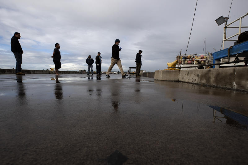 """People keep their distance as they wait in line to buy fish from boat captain Nick Haworth, second from right, Friday, March 20, 2020, in San Diego. Haworth came home to California after weeks at sea to find a state all but shuttered due to coronavirus measures, and nowhere to sell their catch. A handful of tuna boats filled with tens of thousands of pounds of fish are now floating off San Diego's coast as they scramble to find customers. Haworth was selling on Friday to individuals for less than half what he would get from wholesalers. """"This is a quarantine special,"""" he joked. (AP Photo/Gregory Bull)"""