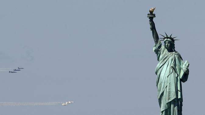 Skuadron jet tempur Blue Angels dari Angkatan Laut dan Thunderbirds dari Angkatan Udara Amerika Serikat bermanuver di langit Kota New York, Selasa (28/4/2020). Aksi tersebut sebagai bentuk penghormatan untuk petugas medis yang tengah berjuang melawan virus corona COVID-19. (AP Photo/Kathy Willens)