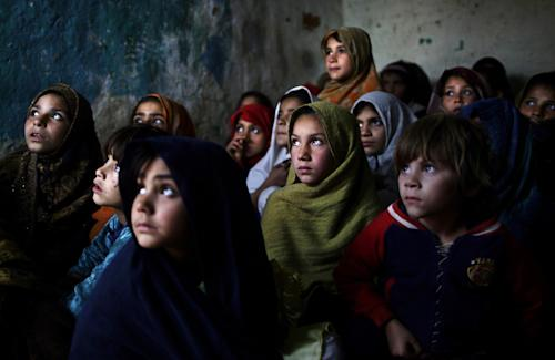 In this Thursday, Jan. 31, 2013, photo, Pakistani schoolgirls, who were displaced with their families from Pakistan's tribal areas due to fighting between militants and the army, listen to their teacher, not seen, while a health worker visiting their school to give polio vaccines, in a poor neighborhood on the outskirts of Islamabad, Pakistan. Wonder Woman and Supergirl now have a Pakistani counterpart in the pantheon of female superheroes _ one who shows a lot less skin. Meet Burka Avenger: a mild-mannered teacher with secret martial arts skills who uses a flowing black burka to hide her identity as she fights local thugs seeking to shut down the girls' school where she works. Sadly, it's a battle Pakistanis are all too familiar with in the real world.(AP Photo/Muhammed Muheisen)
