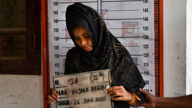 Pengungsi etnis Rohingya memegang papan berisi identitasnya saat pendataan di pusat penampungan sementara bekas kantor Imigrasi Punteuet di Lhokseumawe, Aceh Utara (26/6/2020). (AFP Photo/CHAIDEER MAHYUDDIN)
