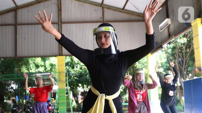 Penari tradisional dari Sanggar Eschoda melakukan latihan menggunakan masker dan pelindung wajah di Kota Tangerang, Jumat (12/6/2020). Para penari itu menerapkan protokol kesehatan jelang new normal atau tatanan hidup normal, sekaligus sebagai upaya pencegahan Covid-19. (Liputan6.com/Angga Yuniar)
