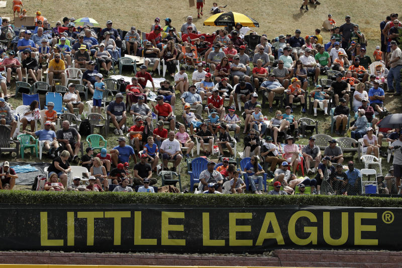 In this Aug. 24, 2019, photo, Little League fans watch from the hillside overlooking left field at Lamade Stadium during the International Championship baseball game between Curacao and Japan at the Little League World Series tournament in South Williamsport, Pa. Little League has been benched. The youth baseball program that boasts more than 2.5 million kids spread over 6,500 programs in 84 countries is on hold at least until May 11 due to the corona virus pandemic. Even that target date for a return to the sports lineup seems optimistic, and the fate of its signature event, the Little League World Series in August in South Williamsport, Pennsylvania is unclear. (AP Photo/Gene J. Puskar)