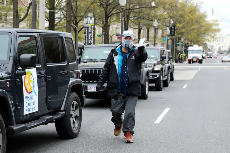FILE PHOTO: Andres offers a pair of masks to a reporter as he prepares with members of his World Central Kitchen team to load meals to deliver to people in need during the coronavirus outbreak in downtown Washington