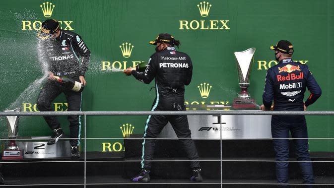 Pembalap Mercedes Lewis Hamilton (tengah) melakukan selebsasi usai menempati posisi pertama Formula 1 Grand Prix di Spa-Francorchamps, Spa, Belgia, Minggu (30/8/2020). Posisi kedua dan ketiga diisi pembalap Mercedes Valtteri Bottas serta pembalap Red Bull Max Verstappen. (John Thys, Pool via AP)