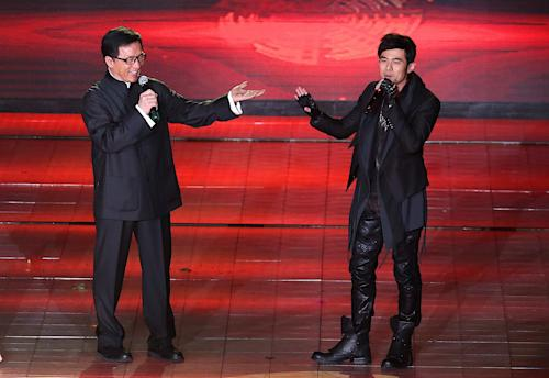 Hong Kong actor Jackie Chan, left, jokes with Taiwanese singer Jay Chou, right, as they perform at the award ceremony for the Beijing Film Festival in Beijing Tuesday April 23, 2013. (AP Photo) CHINA OUT