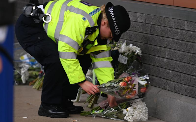 A police officer moves the floral tributes from outside the Croydon Custody Centre - DANIEL LEAL-OLIVAS/AFP via Getty Images