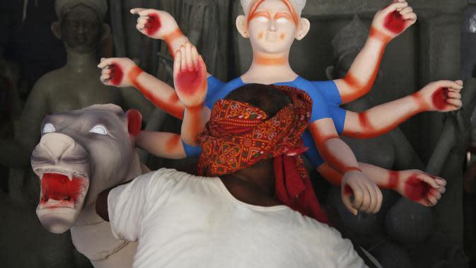 Pematung Nepal Puran Pandit memberikan sentuhan akhir pada patung dewi Hindu Durga menjelang festival Dashain di Kathmandu, Nepal (14/10/2020). Keluarga Pandit akan menjual setidaknya 200 patung untuk festival ini, tetapi tahun ini hanya menjual 20 patung karena pandemi. (AP Photo/Niranjan Shrestha)