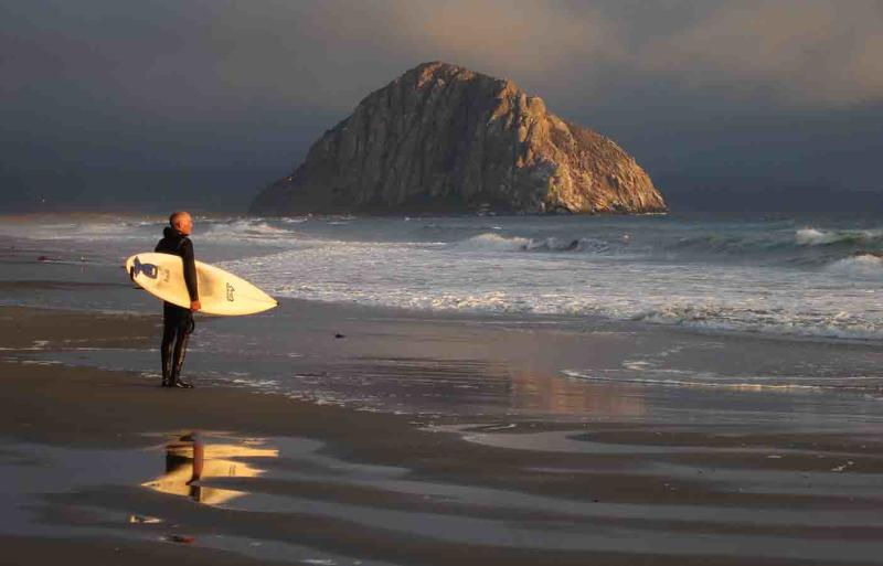 A surfer stands at the edge of the water.