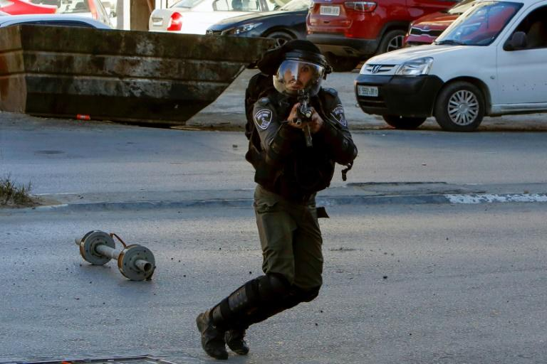 An Israeli border guard aims his rifle towards Palestinian protesters during a raid near the West Bank town of Bethlehem