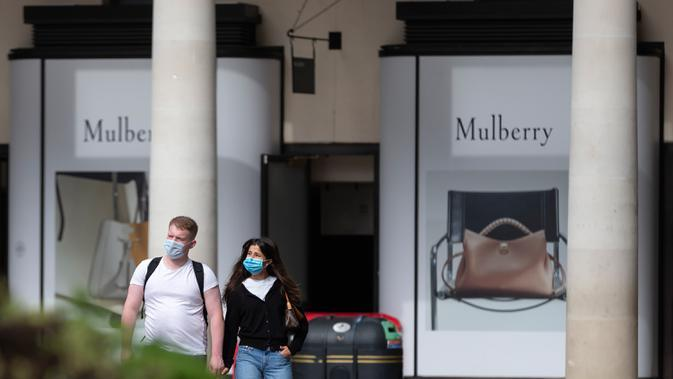 Orang-orang yang mengenakan masker berjalan melewati Covent Garden di London, Inggris, pada 21 September 2020. Menteri Kesehatan Matt Hancock pada Minggu (20/9) mengatakan Inggris mungkin akan menerapkan lebih banyak pembatasan untuk mengatasi penyebaran virus tersebut. (Xinhua/Han Yan)