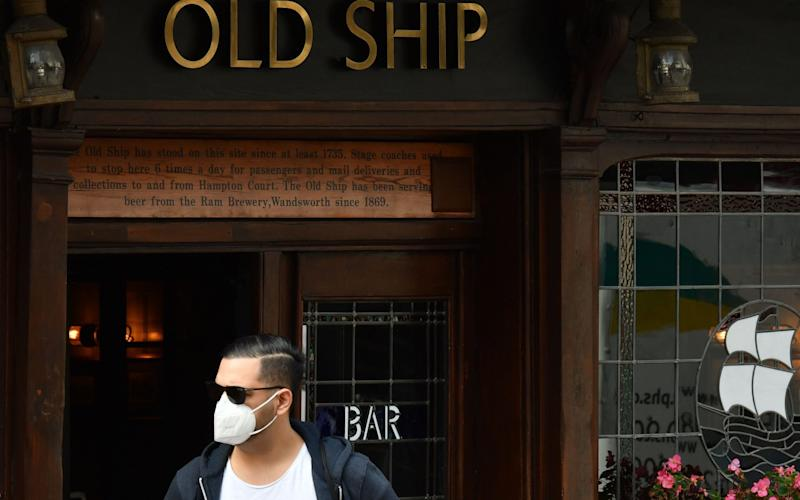 A member of the public wearing a facemask walks past a pub in southwest London on September 19, 2020. - Britain is seeing a second wave of the coronavirus outbreak, Prime Minister Boris Johnson said yesterday, as millions more people faced new restrictions and the government warned that another national lockdown could be imminent - Justin Tallis/AFP