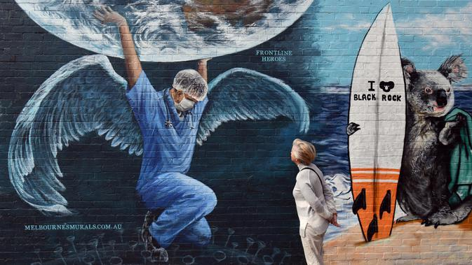 Seorang wanita memandangi mural yang menggambarkan petugas kesehatan dengan sayap memegang bola dunia pada Hari Perawat Internasional di Melbourne,Australia, Selasa (12/5/2020). Petugas medis menghadapi risiko besar di tengah pandemi virus corona COVID-19 seperti sekarang ini. (William WEST/AFP)