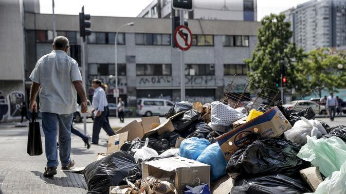 Orang-orang berjalan melewati tumpukan sampah yang diakibatkan pemogokan petugas sampah di Santiago (14/11/2019). Demo yang semakin keras juga disertai aksi mogok nasional termasuk petugas sampah di negara kaya minyak di Amerika Selatan tersebut. (AFP/Javier Torres)