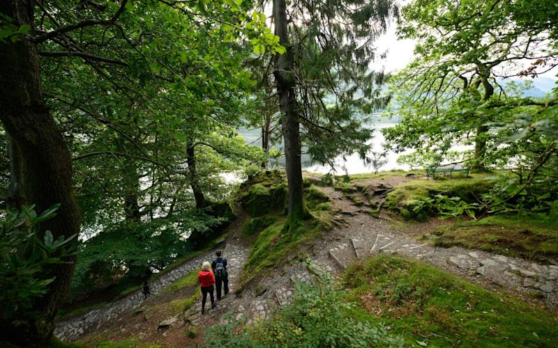 A couple walk along a path beside Ullswater in the sunshine near Glenridding in the Lake District in north west England on Bank Holiday Monday, August 31, 2020, as many people opt to holiday at home rather than risk having to self-isolate for two weeks on return from a foreign holiday - Oli Scarff/AFP