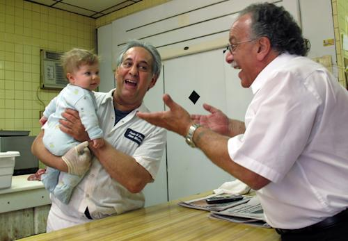 "John Sacco Sr. hands his 6-month-old grandson, Jack Russo, to Pete Canu, a customer in Sacco's Elizabeth, N.J., butcher shop, Thursday, June 20, 2013. Canu says he liked the realism and human flaws of actor James Gandolfini's Tony Soprano character, but Sacco said, ""The Sopranos perpetuated and spread negative stereotypes about Italian-Americans."" Gandolfini died June 19, in Italy, and is being remembered in the northern New Jersey towns where the show was filmed. (AP Photo/Wayne Parry)"