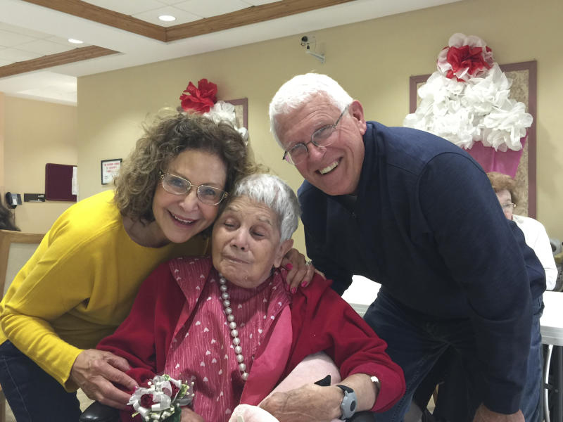 This May 2018 photo provided by Julie Griffith shows Julie Griffith, left, with her mother Mabel Porter, center, and Griffith's husband, David, as they pose for a photo at a nursing home in Oregon, Ohio. The Griffiths are among those advocating to allow cameras inside long-term care facilities. Visitation bans at nursing homes because of the coronavirus have sparked renewed interest in legislation to allow the cameras.(Julie Griffith/Julie Griffith via AP)